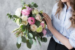 Florist at work: pretty young woman making fashion modern bouquet of different flowers Royalty Free Stock Photos