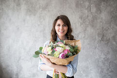 Florist at work: pretty young woman making fashion modern bouquet of different flowers Stock Photo