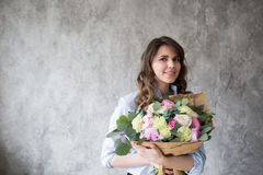Florist at work: pretty young woman making fashion modern bouquet of different flowers Royalty Free Stock Image