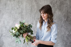Florist at work: pretty young woman making fashion modern bouquet of different flowers Stock Images