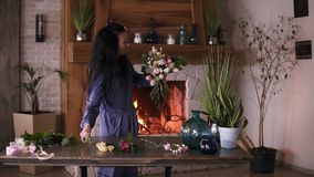Florist at work: professional florist making fashion modern bouquet of different flowers and plants at home studio by. Adding pink tulips to composition. Close stock video footage