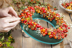 Florist at work: steps of making door wreath