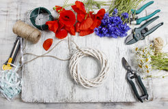 Florist at work. Woman decorating wicker wreath with wild flower Royalty Free Stock Photo