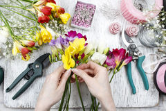 Florist at work. Woman making bouquet of freesia flowers Royalty Free Stock Images