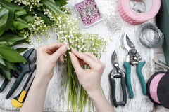 Florist at work. Woman making bouquet of lily of the valley flow Stock Photos
