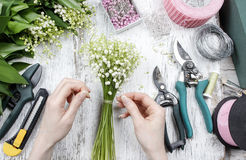 Florist at work. Woman making bouquet of lily of the valley flow. Ers. Festive and party decoration Stock Images