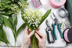 Florist at work. Woman making bouquet of lily of the valley flow Royalty Free Stock Images