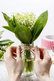 Florist at work. Woman making bouquet of lily of the valley flow Stock Photo