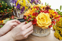 Florist at work: woman making bouquet of orange roses and autumn Stock Images