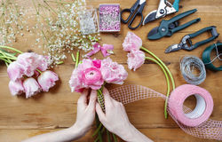 Florist at work. Woman making bouquet of pink persian buttercup Stock Photography
