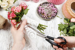 Florist at work. Woman making bouquet of pink roses Stock Image