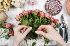 Florist at work. Woman making bouquet of pink roses Stock Images