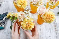 Florist at work. Woman making bouquet of pink roses and yellow c Stock Photo