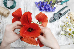 Florist at work. Woman making bouquet of poppies Royalty Free Stock Photography