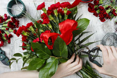 Florist at work. Woman making bouquet of red carnations Royalty Free Stock Images