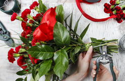 Florist at work. Woman making bouquet of red carnations Stock Photo