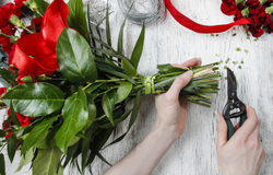 Florist at work. Woman making bouquet of red carnations Royalty Free Stock Image