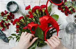 Florist at work. Woman making bouquet of red carnations Stock Photos
