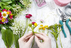 Florist at work. Woman making bouquet of wild flowers. Festive and party decoration Stock Images