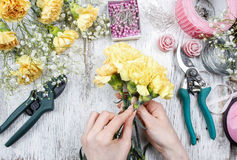 Florist at work. Woman making bouquet of yellow carnations Stock Photography