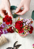 Florist at work. Woman making floral arrangement with red carnat Royalty Free Stock Photography