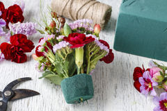 Florist at work. Woman making floral arrangement with red carnat Stock Photo