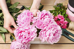 Florist at work: woman making floral decoration of pink peonies Stock Photography