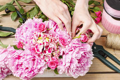 Florist at work: woman making floral decoration of pink peonies Stock Images