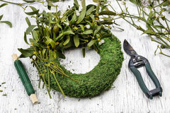 Florist at work: woman making mistletoe wreath Stock Image
