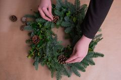 Florist at work: woman making natural Christmas wreath, christmas decorations with natural fir branches stock photo