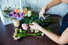Florist at work. Woman making spring floral decorations Royalty Free Stock Photos