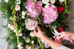 Florist at work. Woman making spring floral decorations the wedding table , the bride and groom. stock image
