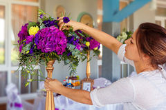 Florist at work. Woman making spring floral decorations the wedding table , the bride and groom. royalty free stock photos