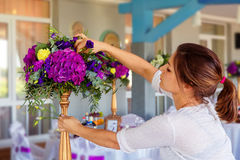 Florist at work. Woman making spring floral decorations the wedding table , the bride and groom. royalty free stock photo