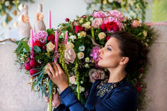 Florist at work. Woman making spring floral decorations the wedding table , the bride and groom. Flowers, candles, a bottle of ch stock images