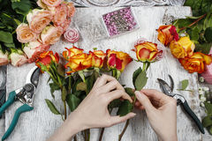 Florist at work. Woman making wedding bouquet of orange roses Royalty Free Stock Photography