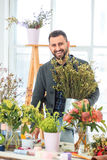 Florist at work: the young MAN making fashion modern bouquet of different flowers Stock Image