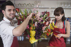 Florist Working With Colleague In Flower Shop. Portrait of male florist working with female colleague in flower shop Royalty Free Stock Photo