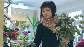 A florist is working in a flower shop. Saleswoman of flowers is creating a new bouquet stock video footage