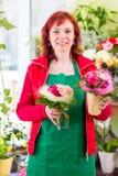 Florist working in flower shop Stock Photo