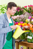 Florist working in flower shop watering plants Stock Photos