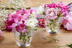 Florist workplace: incomplete tiny bouquets in glass vases. Steps of making floral decorations stock images
