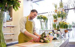 Florist wrapping flowers in paper at flower shop Stock Images