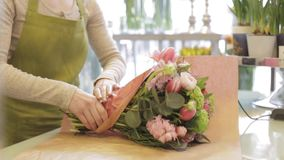 Florist wrapping flowers in paper at flower shop stock video