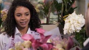 Florista alegre que da la composición de la flor al cliente metrajes