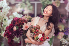 Florista asiático bonito da mulher no vestido branco com o ramalhete das flores nas mãos na loja de flor Imagem de Stock