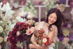 Florista asiático bonito da mulher no vestido branco com o ramalhete das flores nas mãos na loja de flor Foto de Stock Royalty Free