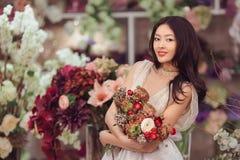 Florista asiático bonito da mulher no vestido branco com o ramalhete das flores nas mãos na loja de flor Imagem de Stock Royalty Free