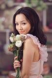 Florista asiático bonito da mulher no vestido cor-de-rosa com o ramalhete das flores nas mãos na loja de flor Fotos de Stock