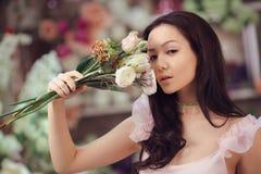 Florista asiático bonito da mulher no vestido cor-de-rosa com o ramalhete das flores nas mãos na loja de flor Imagem de Stock